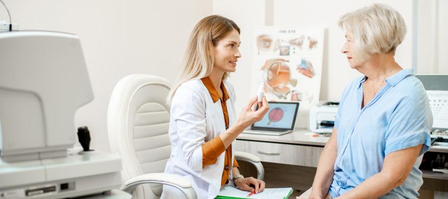 Optometrist showing patient eye drops.